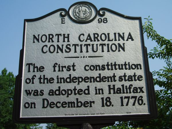 This is a photograph of North Carolina highway historical marker E-98 for the North Carolina Constitution. It is located in Halifax. It reads: North Carolina Constitution. The first constitution of the independent state was adopted in Halifax on December 18, 1776.
