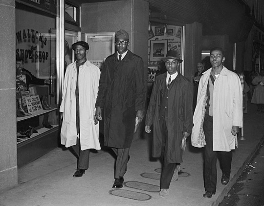 This is a photograph of the Greensboro Four, the four black men who initiated the protest movement of sit-ins in North Carolina by refusing to leave the lunch counter at Woolworth in Greensboro, North Carolina on February 1, 1960.