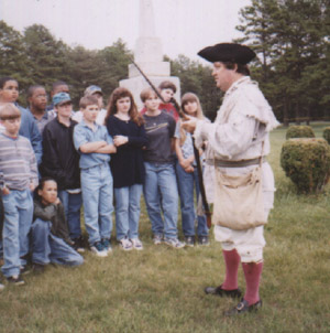 Image of re-enactor with visitors at the Alamance Battleground State Historic Site.