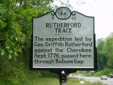 "Image is the historic mile marker for Rutherford Trace. Text reads as follows: ""Rutherford Trace. The expedition led by General Griffith Rutherford against the Cherokee. September 1776, passed her through Balsam Gap."