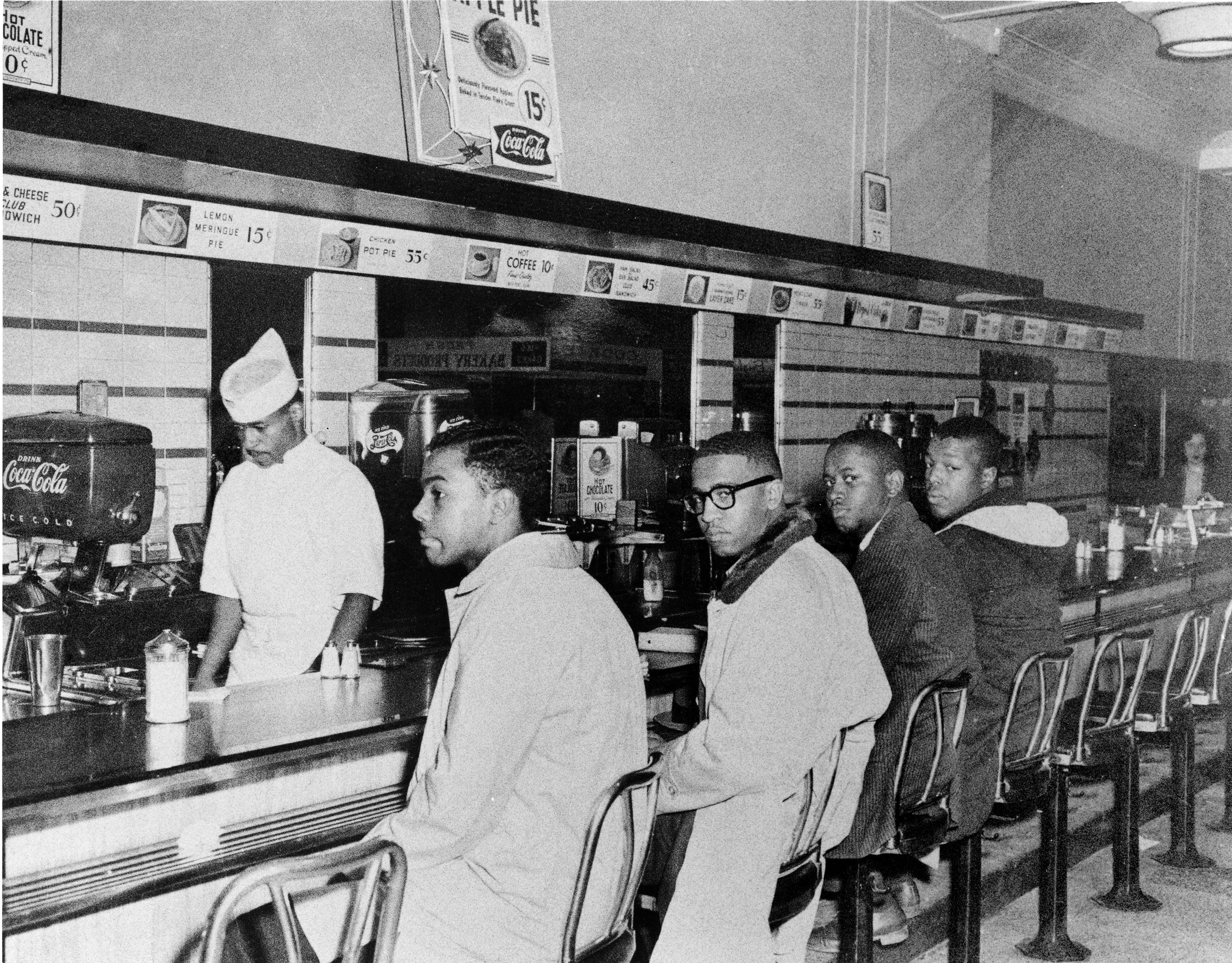 This is a historical photograph of four male African American students sitting at the counter of Woolworth in Greensboro, North Carolina, 1960.