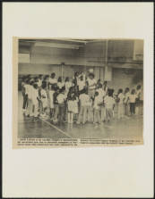 Image of the cover of a report on the Charlotte-Mecklenburg County School System, prepared by the NAACP, Charlotte Branch, 1972-1973. Image shows students playing basketball in a school gynnasium.