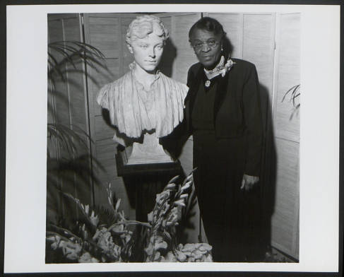 Portrait of Charlotte Hawkins Brown with a sculpture of Alice Freeman Palmer, taken in 1955. Alice Palmer was a friend of Charlotte Hawkins Brown and contributed to fundraising to build the Palmer Memorial Institute. This image is from the collection of the Charlotte Hawkins Brown state historic site.