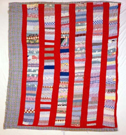 This is a photograph of a quilt made by Eliza Arrington, an African American quilter living in Cary, N.C. around 1930 to 1939. The quilt was pieced in strong and irregular large strips of cloth. It may have been made from a combination of strips of fabric from clothing and feed sacks. This quilt is from the collections of the N.C. Museum of History.