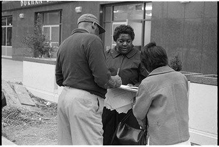 Photograph of Ann Atwater as she registers voters in Durham, N.C. Two individuals stand with her in the picture. They stand in front of a building in Durham.