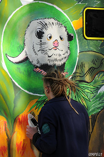 An artist working on a mural for the Leipzig Zoo's Gondwanaland exhibit in May 2011, including a portrait of Heidi the Cross Eyed Opossum. Image from Flickr user Nic Simanek.