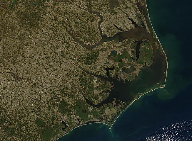 """<img typeof=""""foaf:Image"""" src=""""http://statelibrarync.org/learnnc/sites/default/files/images/NC_coast_sat_no_labels.jpg"""" width=""""653"""" height=""""481"""" alt=""""Map/satellite image of the NC coast/barrier islands"""" title=""""Map/satellite image of the NC coast/barrier islands"""" />"""