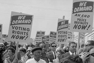 This photograph features black and white people holding signs at the March on Washington, 1963. One sign reads: We demand Voting Rights and is held by a white woman. Another sign reads: We demand an end to police brutality now and is held by a black man.