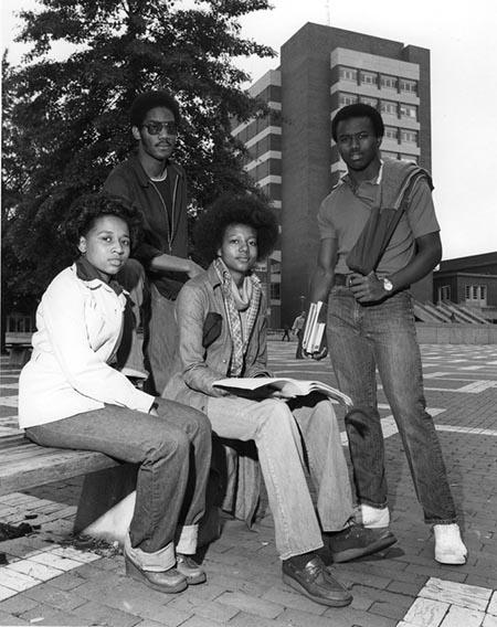 Four African American students sit outside of North Carolina State University's D.H. Hill Library in 1970.