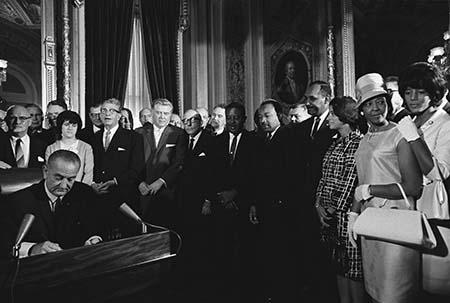 In this photo President Lyndon B. Johnson signs the Voting Rights Act as Martin Luther King Jr. and other civil rights leaders look on, August 6, 1965, United States Capitol, Washington, D.C.