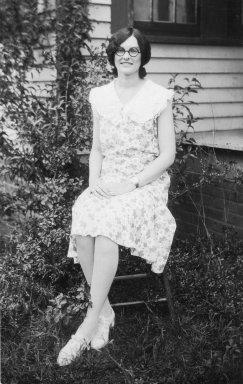 black and white image of a dark-haired young lady sitting on a chair outdoors