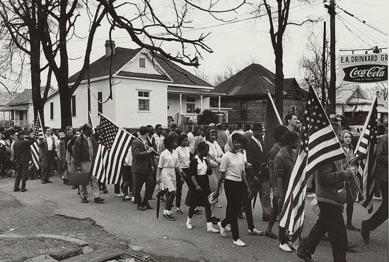 Participants, some carrying American flags, marching in the civil rights march, 1965