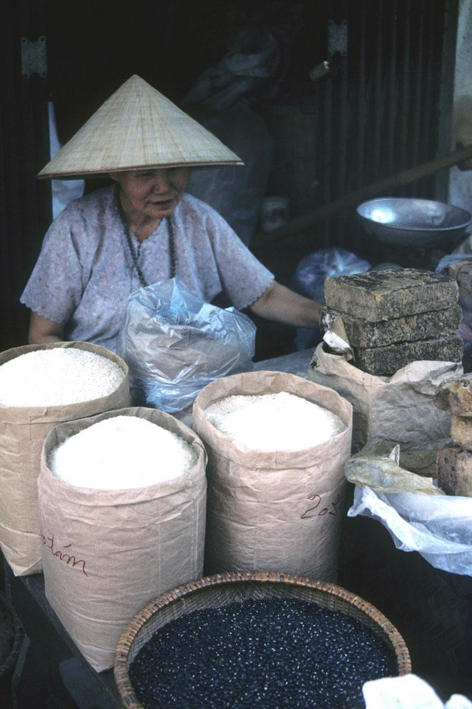 """<img typeof=""""foaf:Image"""" src=""""http://statelibrarync.org/learnnc/sites/default/files/images/vietnam_143.jpg"""" width=""""683"""" height=""""1024"""" alt=""""A woman sells rice from large bags at a Hanoi outdoor market"""" title=""""A woman sells rice from large bags at a Hanoi outdoor market"""" />"""
