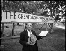 Joe L. Hartley Sr. in front of the Singing on the Mountain sign
