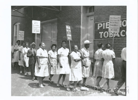 This is a photograph of strikers from United Tobacco Workers Local 22 on the picket line in Winston-Salem, 1946. The picket line grew as supportive employees from other Reynolds plants joined during their lunch hours.