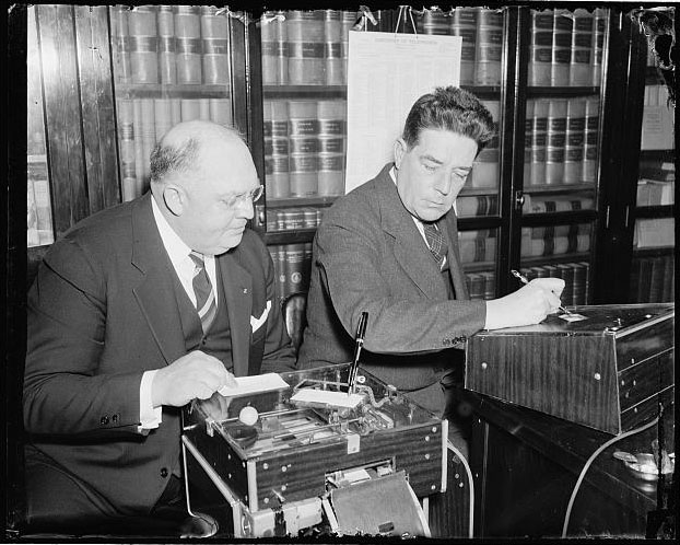 """Demonstrates new signature machine to house member. Washington, D.C., March 18 [1938]. The latest is the automatic electric signature machine invented by Glenn W. Watson, (left) who is shown in this picture demonstrating it to Rep. Lindsay C. Warren of North Carolina."" Presented on Library of Congress."
