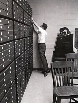 Don Lennon, Coordinator of Special Collections at ECU, reaching for materials in the library archives, circa 1970-1980. Image from Digital Collections, J.Y. Joyner Library, East Carolina University.