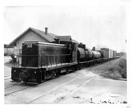 Warehouse and train of the Laurinburg & Southern Railroad, Laurinburg, N.C., 1953. Image from the North Carolina Museum of History.