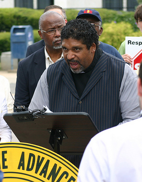 The Reverend Dr. William Barber II, president of the N.C. N.A.A.C.P., speaking across from the legislature building in Raleigh, 2012. Image from Flickr user NC Justice Center.