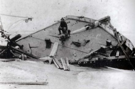 The Priscilla wrecked during the hurricane of 1899. Rasmus Midgett, sitting on the wreckage, saved ten people from the ship during the hurricane.  Image courtesy of the NC Office of Archives and History via East Carolina University.