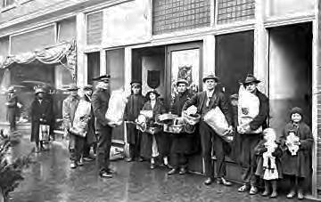 A group of men, women and children outside the Salvation Army with bags, baskets, and toys for the Christmas Revival campaign, Greensboro, N.C., circa 1920-1940). Image from the North Carolina State Archives.