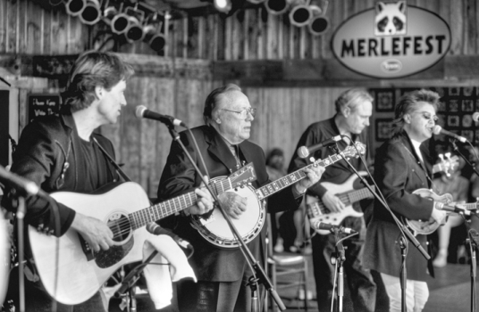 A performance at MerleFest in Wilkesboro, 29 Apr. 2001. Left to right: Brad Davis (guitar), Earl Scruggs (banjo), Gary Scruggs (bass guitar), and Marty Stuart (mandolin). Photograph by David Schenk.