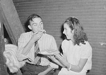 """  Many parents and young people from the school and nearby communities attend the pie and box supper, given by the school to raise money for additional repairs and supplies. Each box or pie is auctioned off to the highest bidder, sometimes bringing a good deal, since the girl's ""boyfriend"" usually wins and has the privilege of eating it with her afterwards."" 1944. Image courtesy Library of Congress."