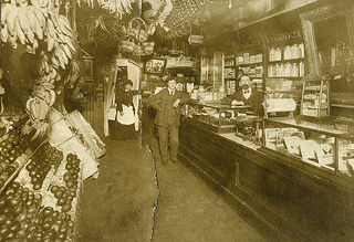 Interior of the Dughi Store,  Interior of the Dughi Store, 235 Fayetteville Street, Raleigh, NC, c.1900; l-r: Elizabeth Foppiano Dughi, her husband, Antonio Leo Dughi (owner), and son,John J. A. Dughi. Bananas and exotic fruits can be seen in the store. From the Dughi Family Photo Collection, PhC.166, North Carolina State Archives, call #: PhC_166_3,  Raleigh, NC.