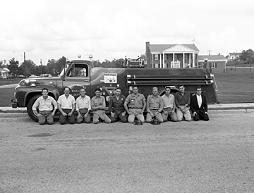Fuquay-Varina Rural Fire Department firemen and equipment, fire truck in 1957. Photo taken on Academy Street in front of the Robert E. Prince Home, Fuquay-Varina, NC. From the Heulon Dean Photo Collection, PhC.133, North Carolina State Archives, call #:  PhC133_1957_142_A.