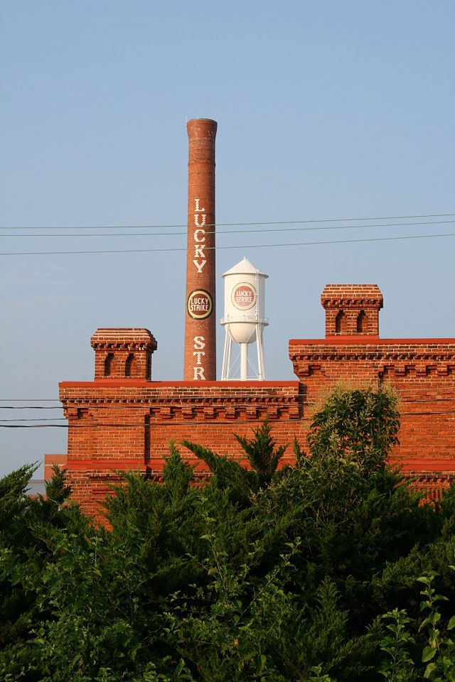 "Ildar Sagdejev . ""Lucky Strike chimney and water tower of the American Tobacco Historic District seen from the railroad in Durham, North Carolina.""  From Wikimedia Commons, used under the GNU Free Documentation License."