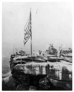 Visitors saluting the flag on Chimney Rock, ca. 1920s.  From the North Carolina State Parks Collection, North Carolina Digital Collections.  Used courtesy of North Carolina State Parks.