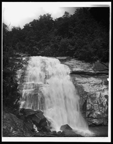 Image of Rainbow Falls, today in Gorges State Park. Photograph ca. 1890-1906. From the Library of Congress Prints and Photographs Online Collection. Item is labeled [Saphhire, N.C., Horse Pasture Falls]. Note that the printed image appears to be a reverse print of the original negative. The horizontal fissure near the top of the falls is actually located on the left, when facing the falls, and a pile of rock and boulders, prominent in the left foreground of the image is actually on the right side of the view when facing the falls.