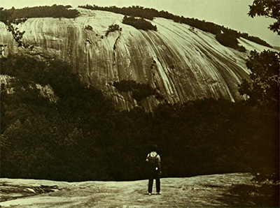Hiker looking up at rock face, Stone Mountain State Park. Stone Mountain State Park Master Plan, 1970, NC Division of Parks and Recreation.