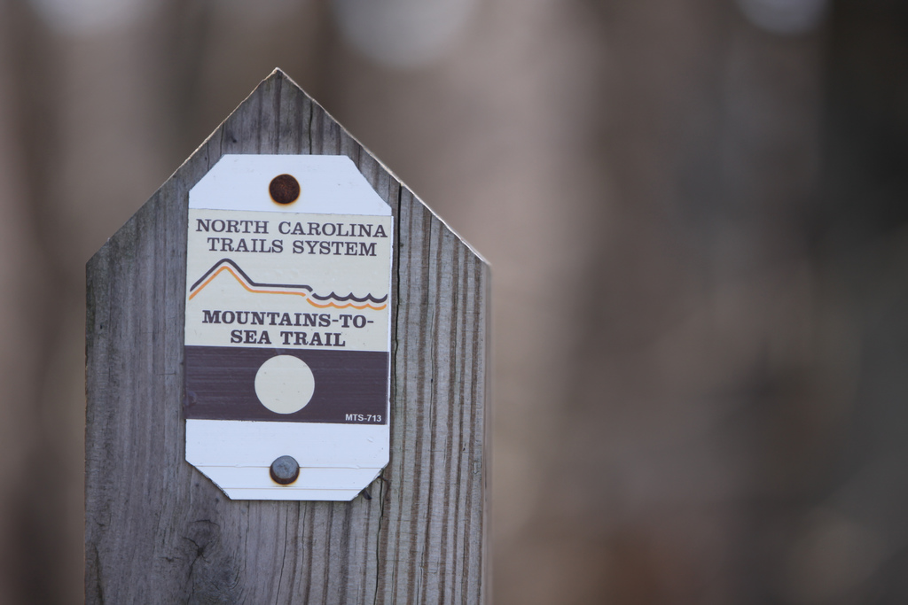 Mountains-to-Sea Trail signpost marks it as a project of the North Carolina Trails System.