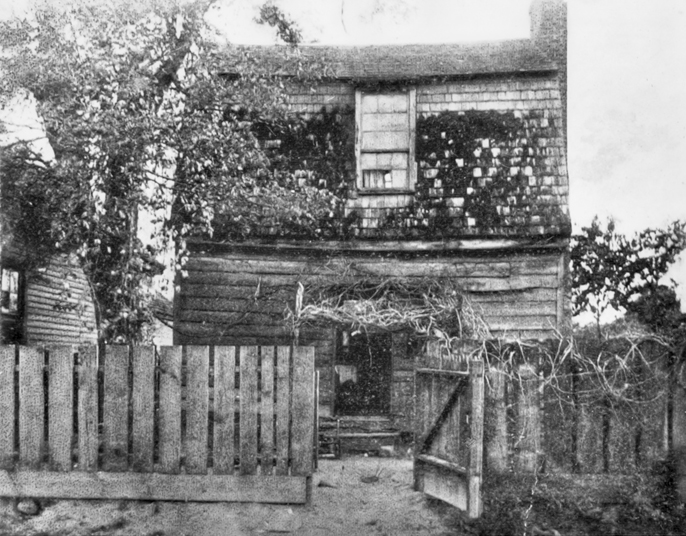 Andrew Johnson's birthplace, ca. 1906. The photograph was likely taken before the house was moved from its original site. North Carolina Collection, University of North Carolina at Chapel Hill Library.