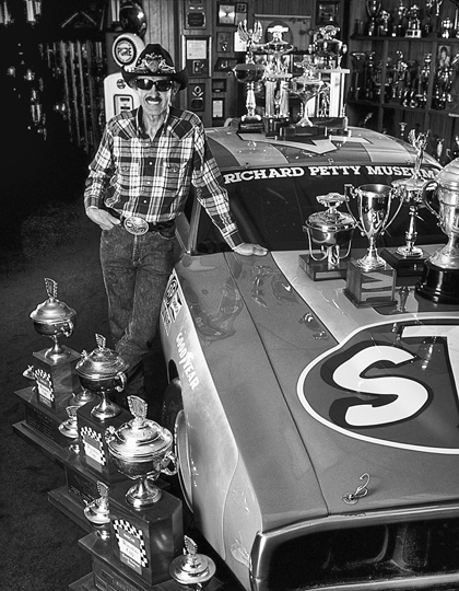 Richard Petty with one of his race cars and some of his many trophies in the Petty Museum at Level Cross. Photograph courtesy of the North Carolina Division of Tourism, Film, and Sports Development.