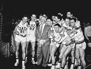 Everett Case, nicknamed the Old Gray Fox, and his North Carolina State basketball team after defeating Wake Forest 82-80 at Reynolds Coliseum in Raleigh to win the first ACC title on 6 Mar. 1954. Raleigh News and Observer.