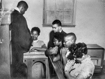 Durham pastor and civil rights leader Douglas E. Moore gives communion to five of the local youths who sat-in at the Royal Ice Cream Company shop in 1957. Courtesy Virginia Williams and the Civil Rights Heritage Project, Durham County Library.