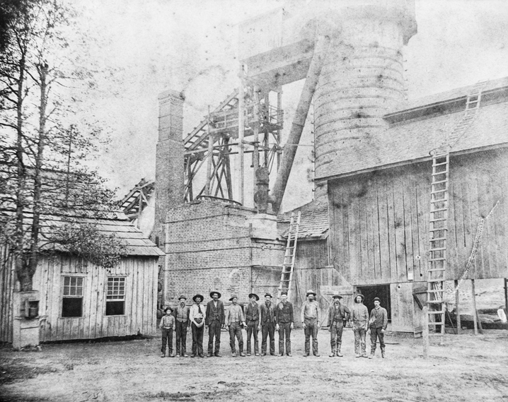 Employees stand in front of the furnace of the Cranberry Iron Mine, ca. 1895. North Carolina Collection, University of North Carolina at Chapel Hill Library.