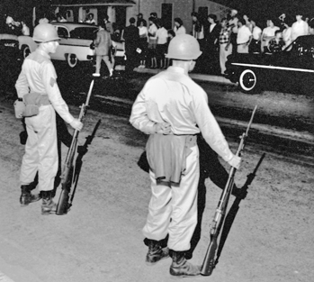 Photograph, National Guardsmen face off with townspeople in Henderson after being mobilized by Governor Luther Hodges during the Harriet-Henderson Mills strike in May 1959. Courtesy of North Carolina Office of Archives and History, Raleigh. The Raleigh News and Observer files.