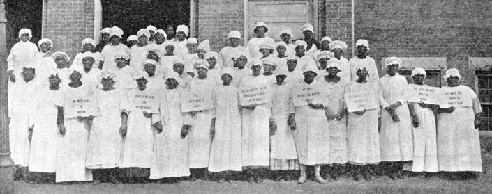 "North Carolina's ""first class of law controlled and class instructed midwives"" on the steps of the Beaufort County Courthouse, 1925. Several of the women hold signs printed with lessons they have learned, such as ""The New Midwife Must Be Clean"" and ""We Must Report the Baby's Birth."" North Carolina Collection, University of North Carolina at Chapel Hill Library."