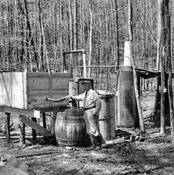 A law enforcement officer pauses after a raid on an illegal liquor distillery in the Eno Township of Orange County in 1958. Photograph by Roland Giduz. North Carolina Collection, University of North Carolina at Chapel Hill Library.