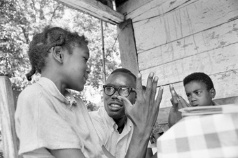 A community worker for the North Carolina Fund teaches math to two children on the front porch of their home near Boone in 1964. Photograph by Billy Barnes. North Carolina Collection, University of North Carolina at Chapel Hill Library.