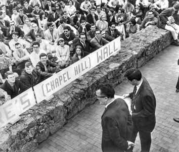Banned speaker Frank Wilkinson (left) is introduced by student body president Paul Dickson from a public sidewalk on Franklin Street as students seated on the UNC campus listen, 2 Mar. 1966. Photograph by Jock Lauterer. North Carolina Collection, University of North Carolina at Chapel Hill Library.