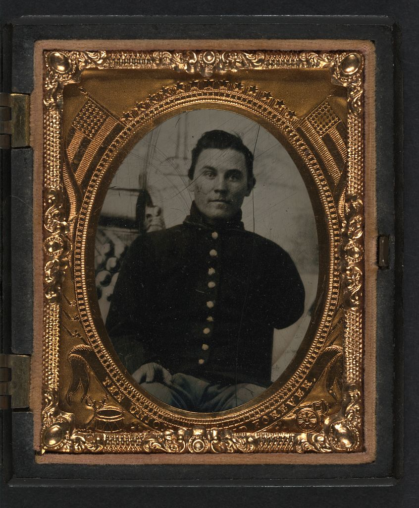 Unidentified soldier with amputated arm in Union uniform in front of painted backdrop showing cannon and cannonballs