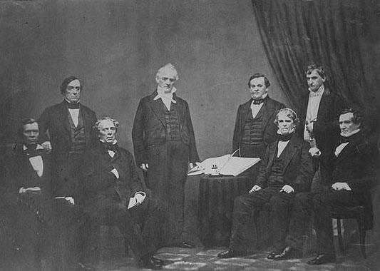 """Buchanan, Pres. & cabinet. Photograph shows President Buchanan standing, surrounded by his Cabinet including Jacob Thompson, Secretary of the Interior; Lewis Cass, Secretary of State; Howell Cobb, Secretary of the Treasury; Jeremiah Black, Attorney General; Horatio King, Postmaster General; John B. Floyd, Secretary of War and Isaac Toucey, Secretary of the Navy."" Presented on Library of Congress."