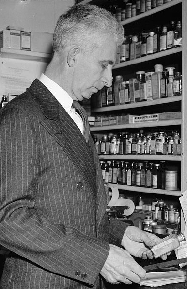 "Harris & Ewing. ""Only Druggist in Congress. Washington, D.C., Feb. 13. While many professions and businesses are represented in the 76th Congress, Rep. Carl T. Durham, democrat of North Carolina, is the only pharmacist in that august body. He ran a drug store at Chapel Hill before his election to the house, 2-13-39"". Photograph. 1939 February 13. LC-H22-D- 5782. Prints and Photographs Division, Library of Congress."