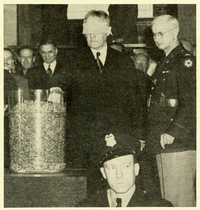 Photograph of Col. John D. Langston (right) with U.S. Secretary of War Henry Stimson (left).  Stimson is drawing a capsule in the selective service lottery on March 17, 1942.  From the March 1942 issue of <i>Selective Service</i>, page 1, published by the National Headquarters, Selective Service System, Washington, D.C. Presented on Archive.org.