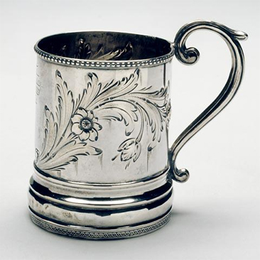 Photograph of sterling silver mug made by Traugott Leinbach, circa 1861-1865, showing floral repousse and engraved cartouche. Used by John Lawson Wrenn.  Item H.1933.4.1 from the collections of the North Carolina Museum of History.  Used courtesy of the North Carolina Department of Cultural Resources.