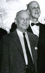 A 1958 photograph of McDaniel Lewis, when he was a member of the Executive Board of the N.C. Department of Archives and History. Behind him is Dr. Christopher Crittenden, head of the department. Image from the North Carolina Museum of History.